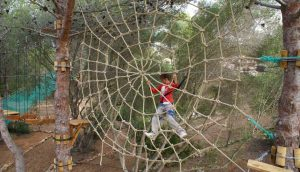 A girl climbing the spider net in Jungle Parc Junior